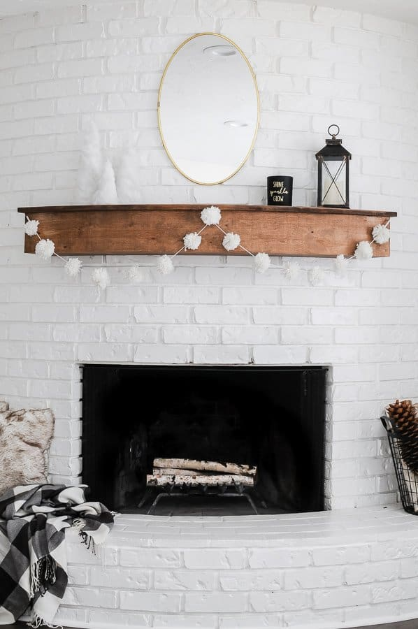 White fireplace with wood mantel and a diy yarn pom pom garland hung on the front.