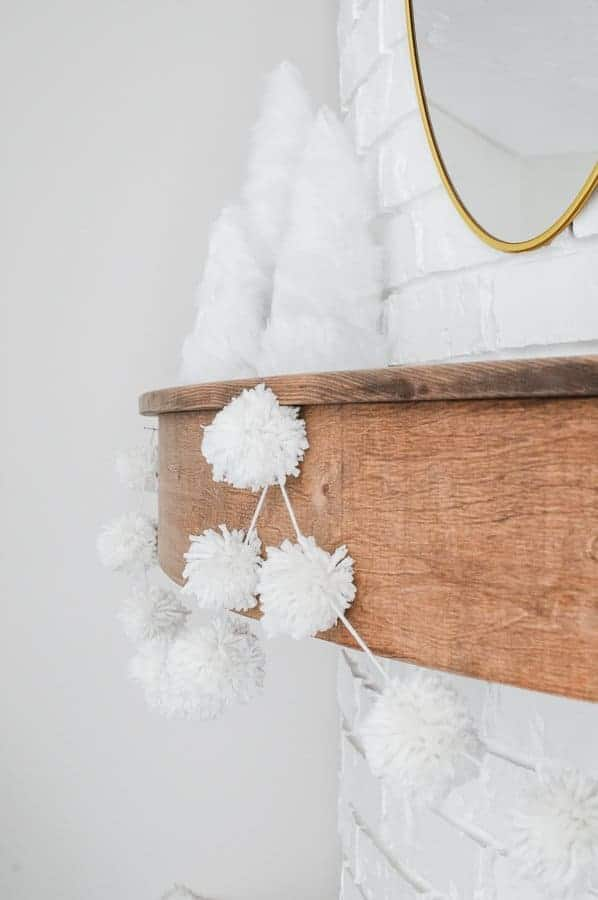 White pom pom garland made out of yarn hung on a wood mantel.