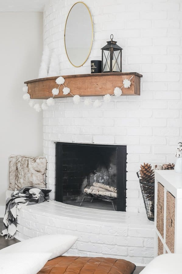 Side angle of a white fireplace with wood mantel and diy yarn pom pom swagged along the front.