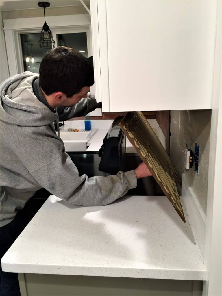 Man installing a faux brick backsplash panel.