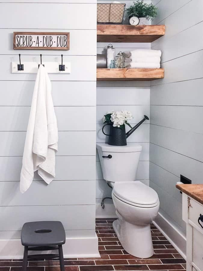Room makeover on a modern rustic farmhouse bathroom with blue shiplap and brick floor.