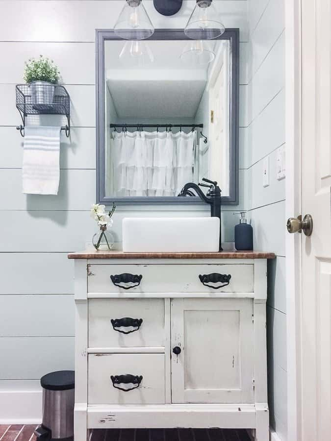 Custom distressed vanity and farmhouse decor in a modern rustic bathroom room makeover.
