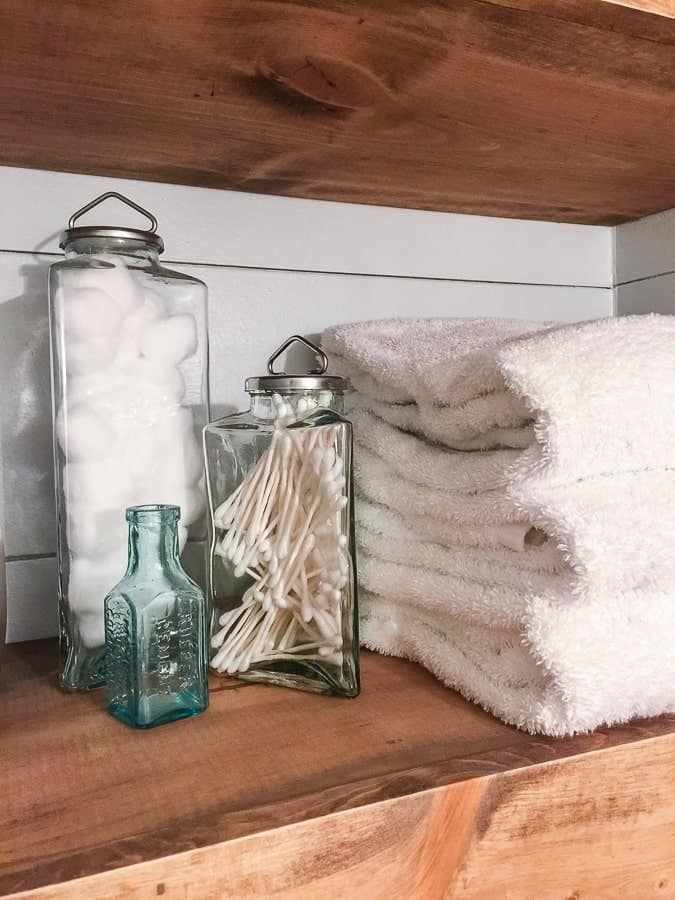 White towels and jars of paper products on a floating shelf in a modern rustic bathroom.