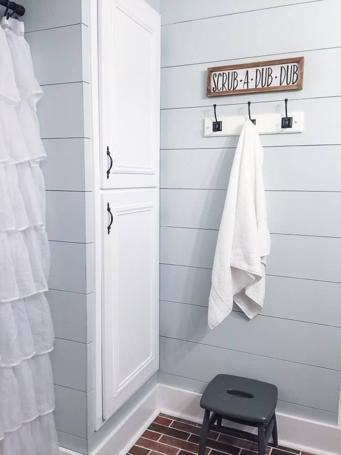 Ruffled shower curtain, white cabinetry and a shiplap wall in a modern farmhouse bathroom room makeover.