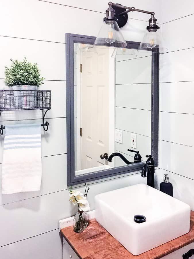 Industrial vanity light and vessel sink in a modern rustic bathroom.