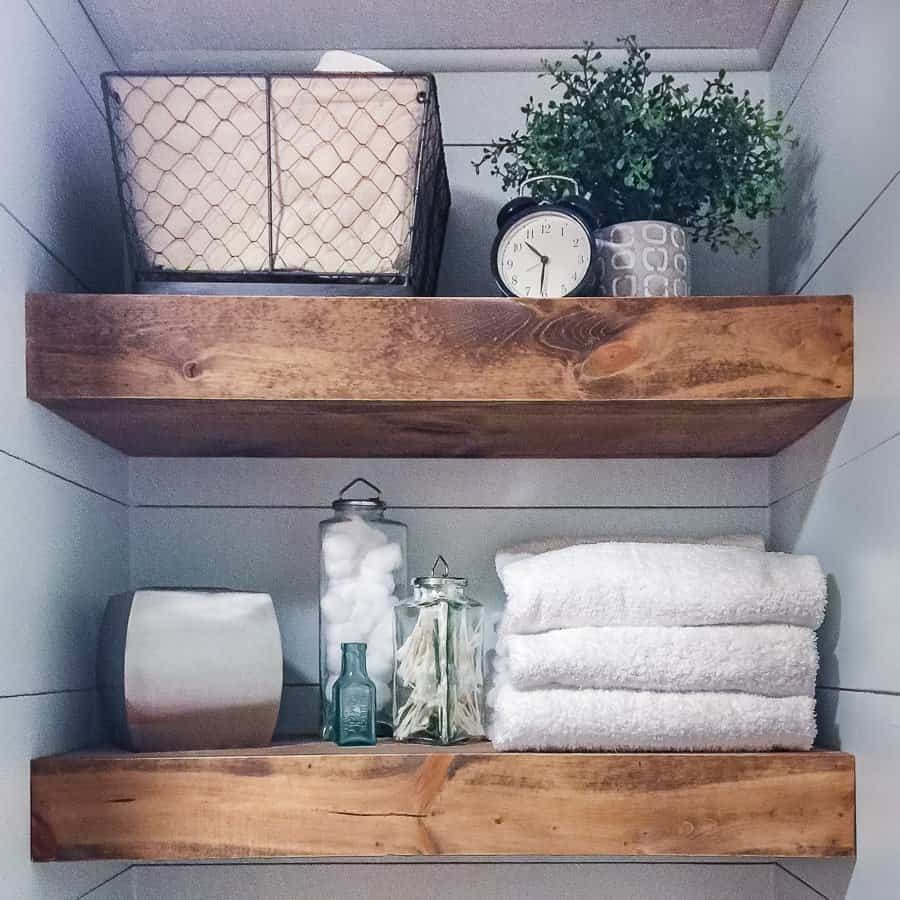 Wood floating shelves in the toilet cubby of a modern rustic bathroom.