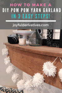 Wood mantel with black, white and blue decor atop and a white pom pom yarn garland hanging on it.