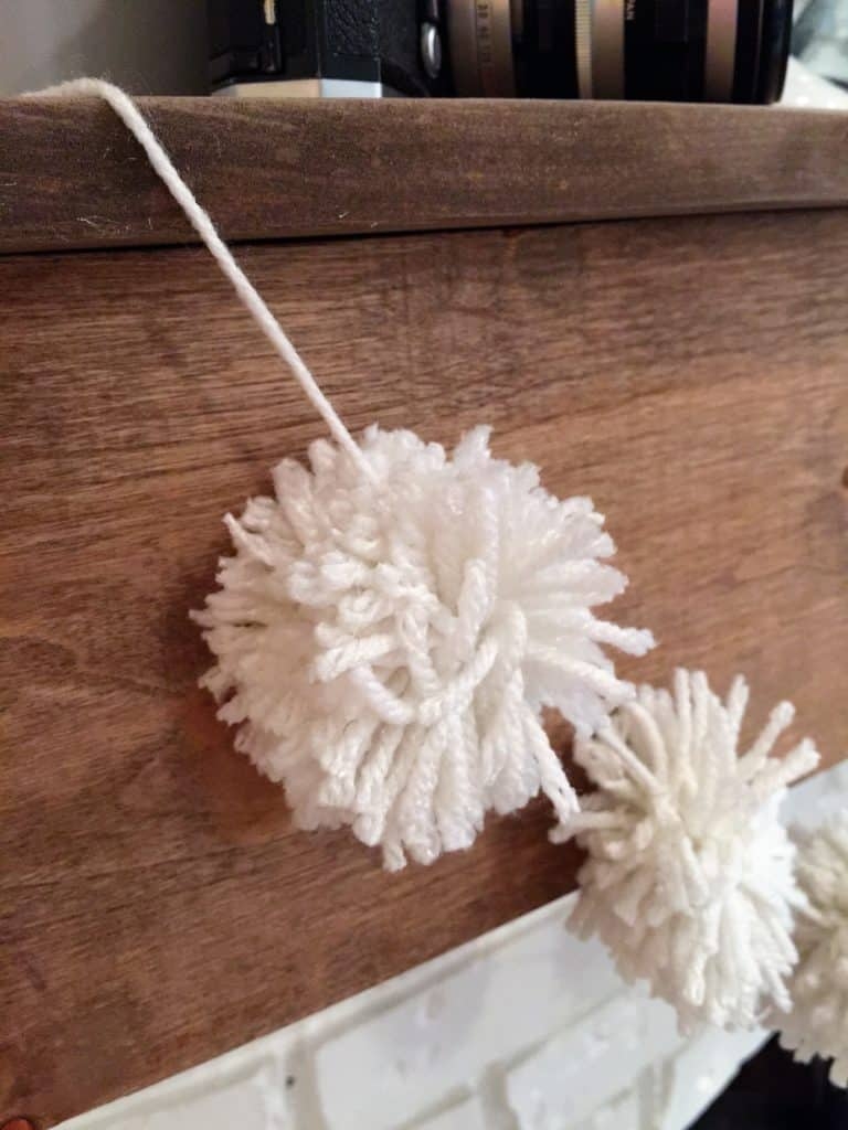 Close up view of yarn pom pom on a garland hung on a mantel.