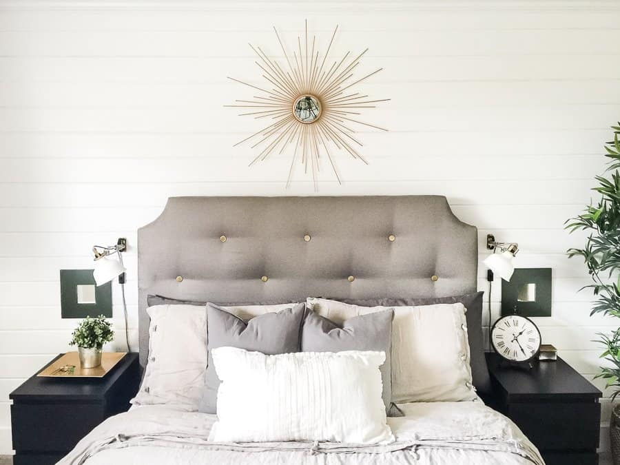 Straight on view of upholstered bed against a shiplap wall with a gold diy starburst mirror above.