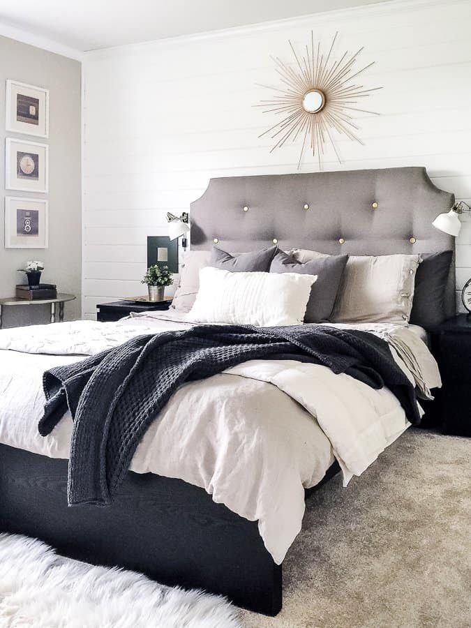 Neutral bed with upholstered headboard on a white shiplap wall with a sunburst mirror above.
