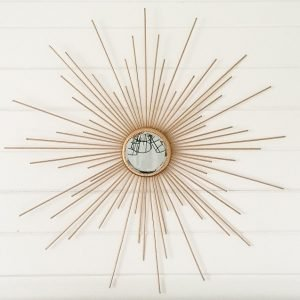 Gold DIY sunburst mirror hanging on white shiplap.