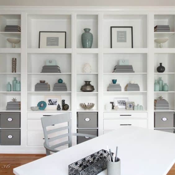 White open shelves along a wall with blue and grey decor.
