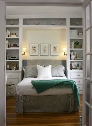 Open shelving towers on either side of a bed.