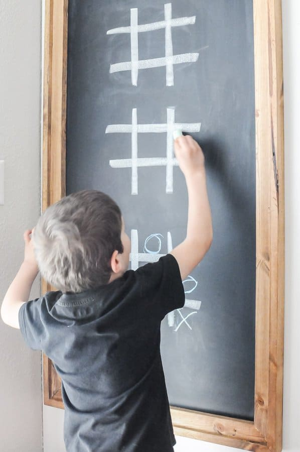 "A young boy reaching to write an ""X"" in tic-tac-toe on a large diy framed chalkboard."