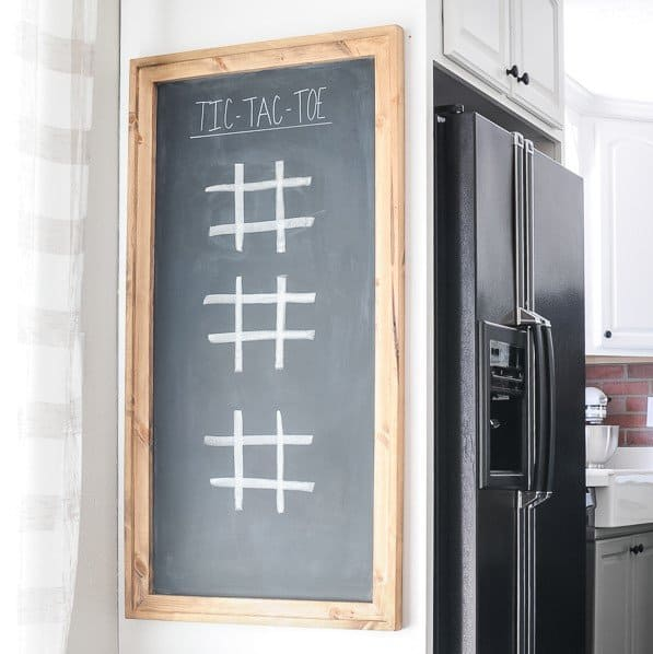 Large wood framed chalkboard with tic-tac-toe on it hanging on the outside cabinet of a kitchen fridge.