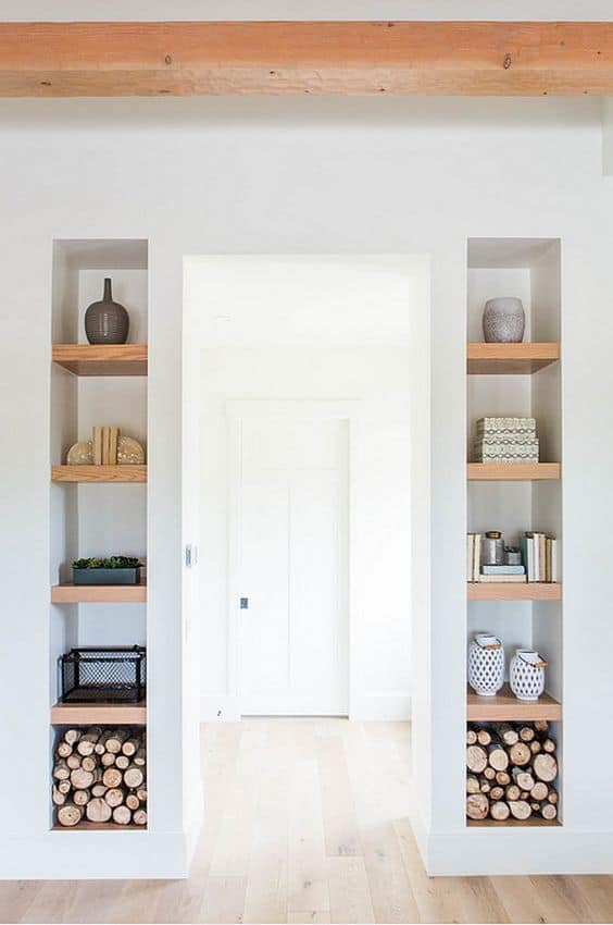 Built-in floating shelves on either side of a hallway entrance.