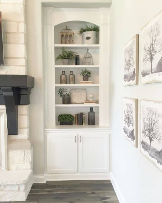 White built-in shelves next to a chunky fireplace mantel.