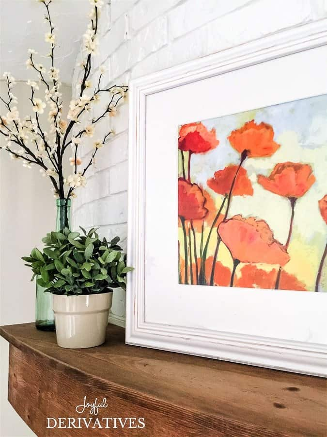 Blossoms in farmhouse vase and floral print spring mantel ideas.