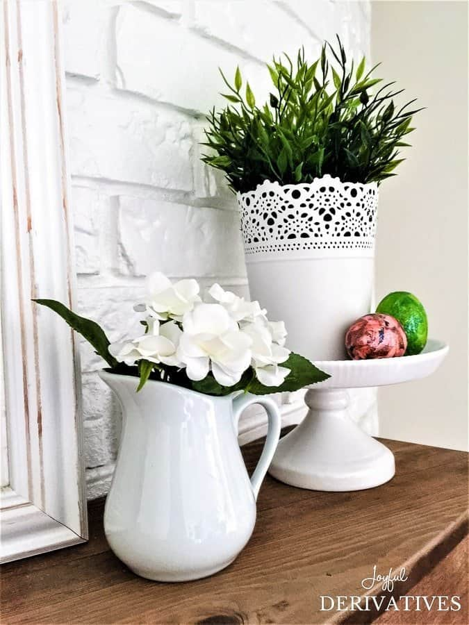 White pitcher and greenery on cake stand spring mantel ideas.