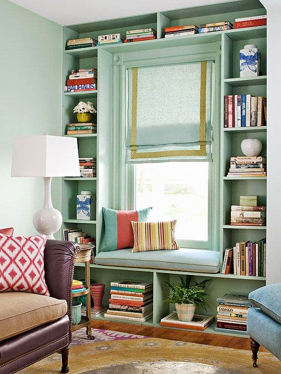 A teal window seat surrounded by open shelves filled with books.