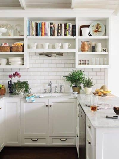 White kitchen with open shelves above the sink.