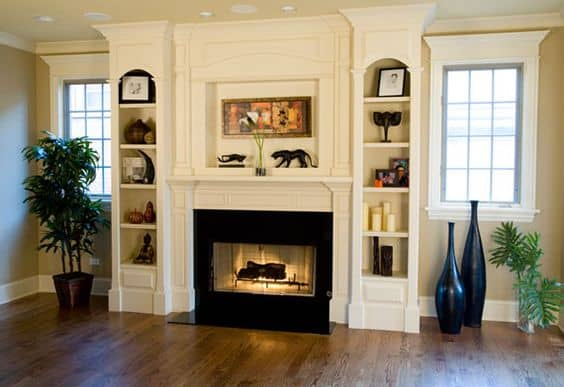 Fireplace mantel with shelving towers built in on either side.