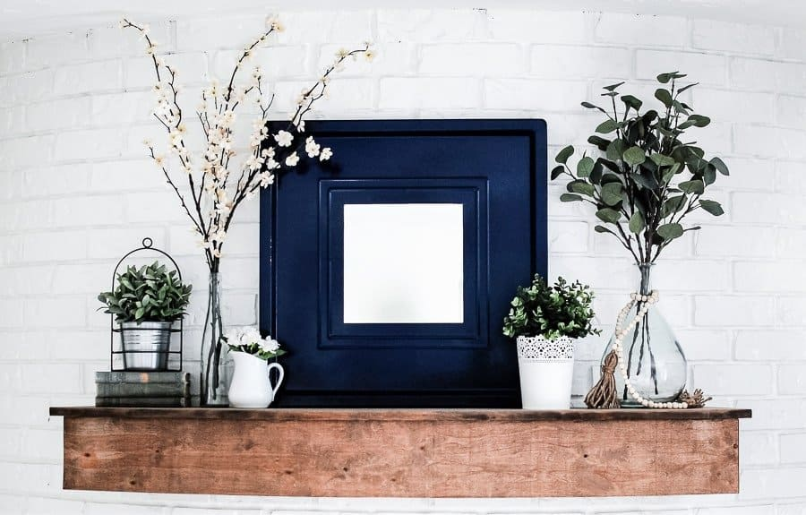 Summer mantel decorating ideas like large mirror and lots of greenery.