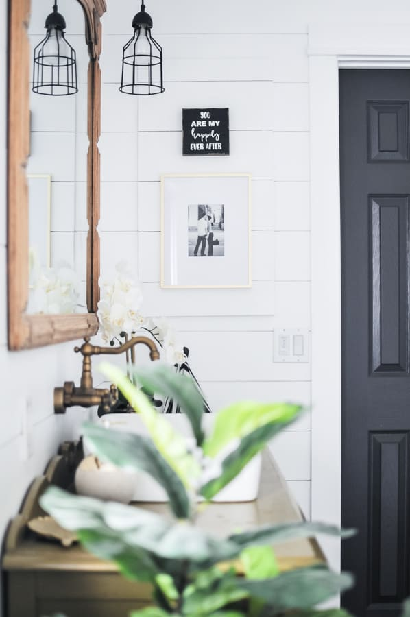 White shiplap bathroom with a diy jewelry cabinet hidden behind pictures on the wall.