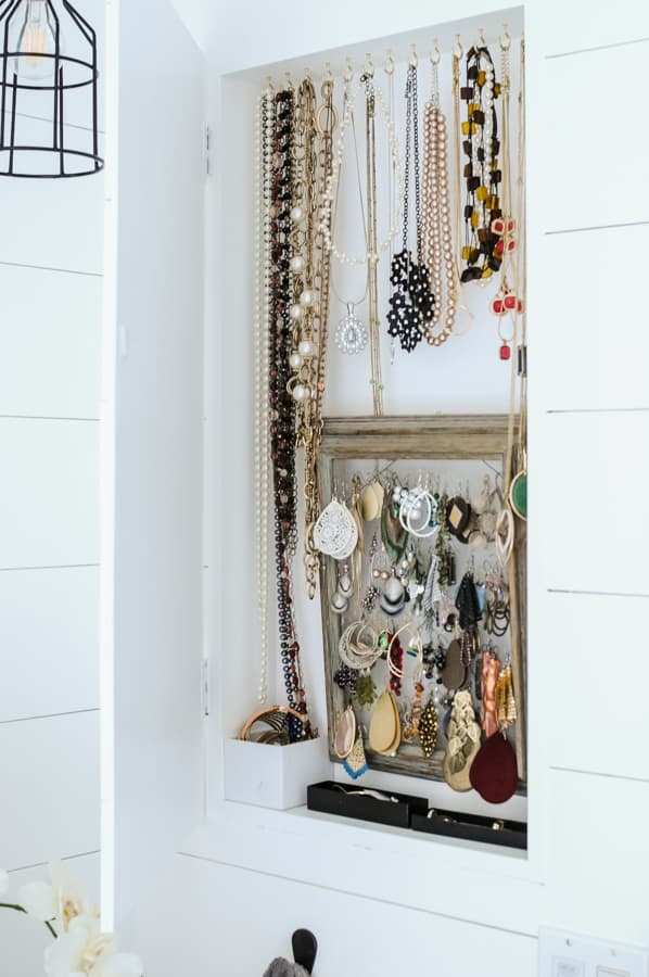 Inside view of jewelry organized on hooks and hangers in a recessed jewelry cabinet.