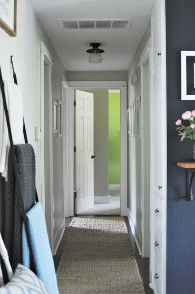 Hallway with white doors, cream walls, a jute rug and an air intake on the ceiling that needs cleaning to improve the air quality in the home.