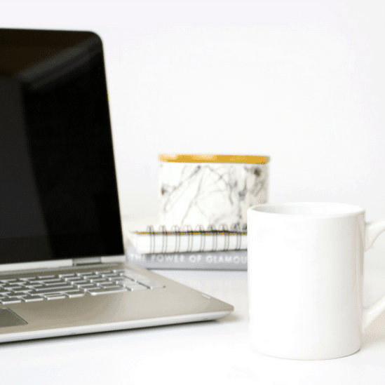 Laptop sitting on a white desk next to a stack of notebooks and a white mug.