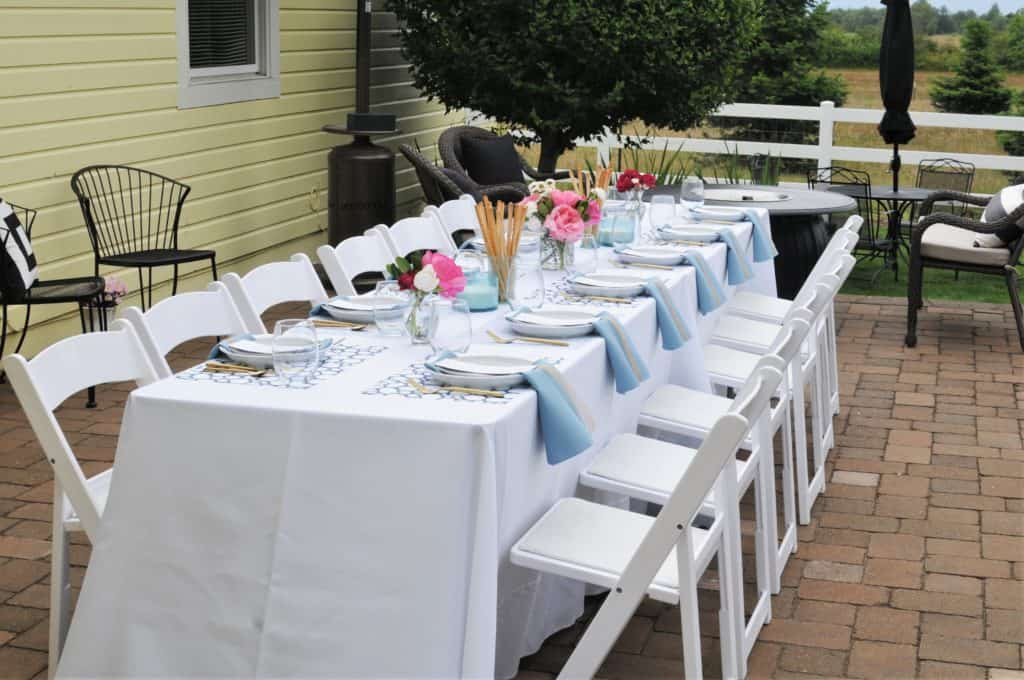 Family-style table with white table cloths and white chairs set for a formal summer luncheon.