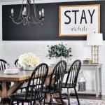 Modern farmhouse dining room with a wood table, black chairs, white shiplap and a black wall with a painted wood sign.