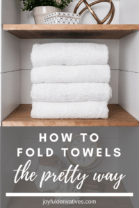 White towels folded nicely on a wood shelf.