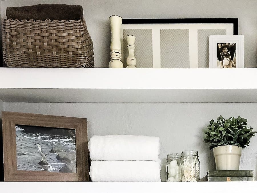 Narrow white floating shelves with bathroom storage in a tutorial for how to fold towels.