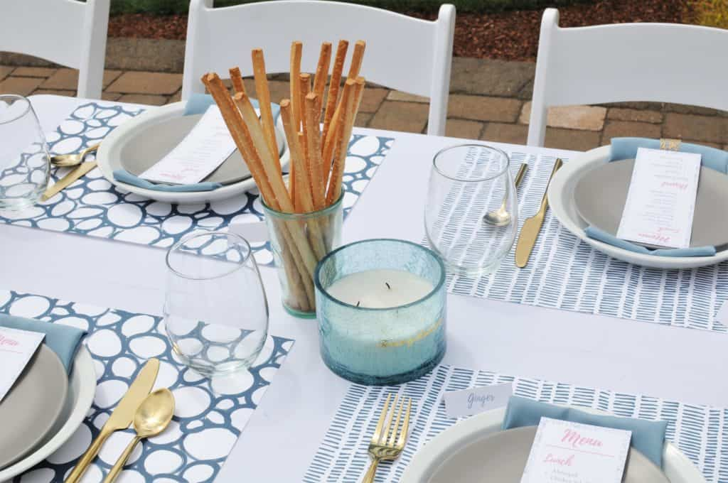 Blue candle and breadsticks on a formal summer luncheon table.