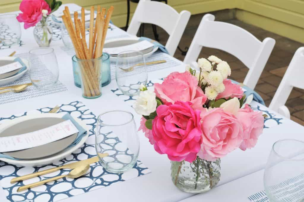 Bright pink floral bouquet on a summer luncheon table.