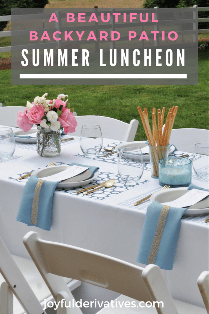 Formally set table outdoors for a summer luncheon with white linens and pink flowers.