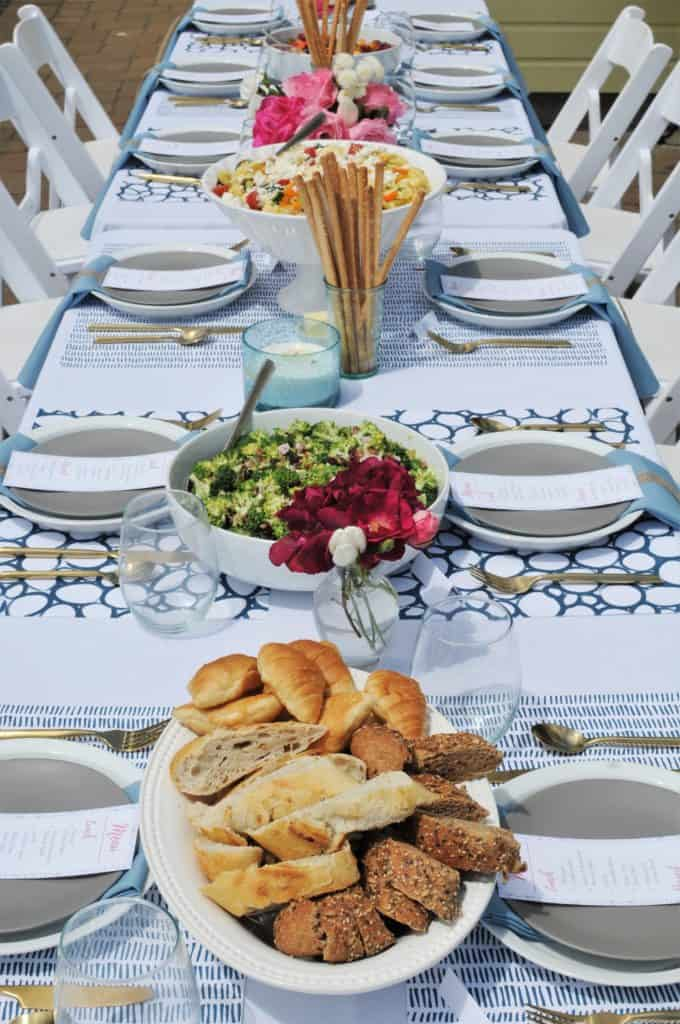 Long family-style summer luncheon table with food.