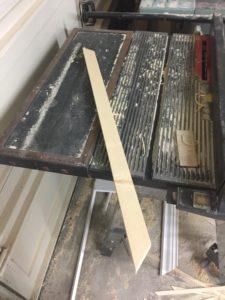 Miter cut 1x2 board sitting on a table saw.