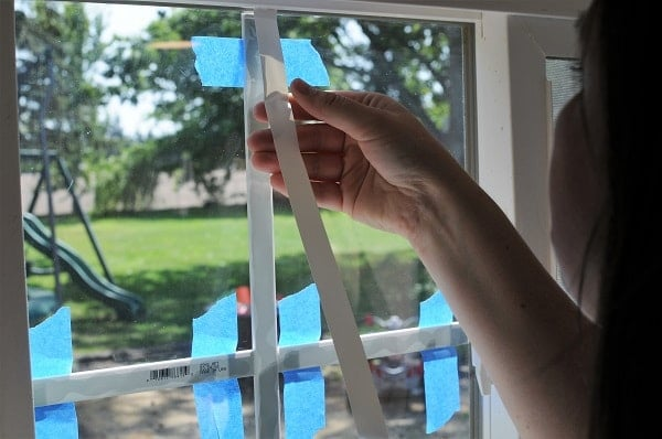 Starting at the top, install a window grid on the inside using electrical tape.