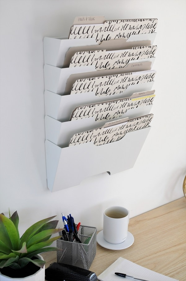 She shed organizing with white wall-mount file sorter.