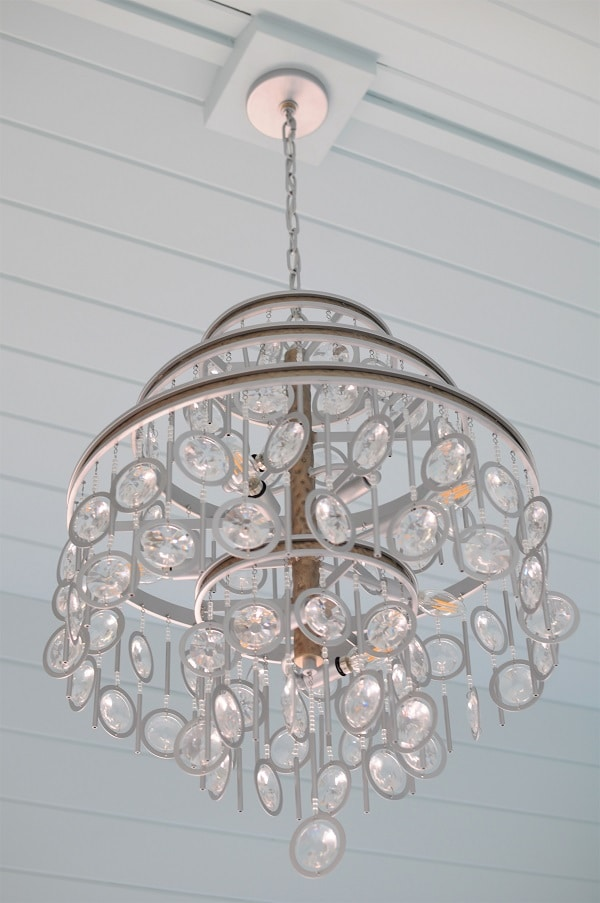 Crystal chandelier with blue shiplap ceiling.
