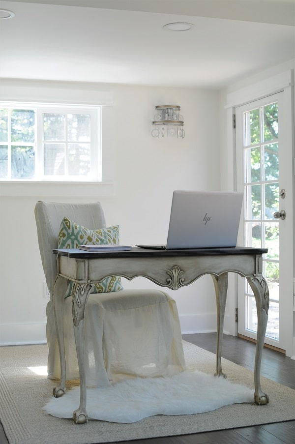 Clawfoot desk, natural and faux sheepskin rugs, and white walls in the she shed home office.