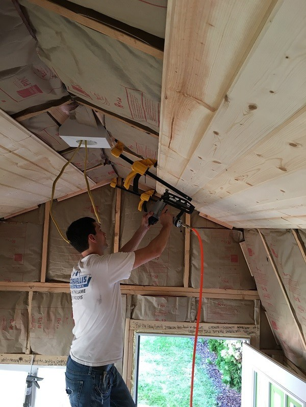 Chris installing shiplap ceiling in she shed home office.