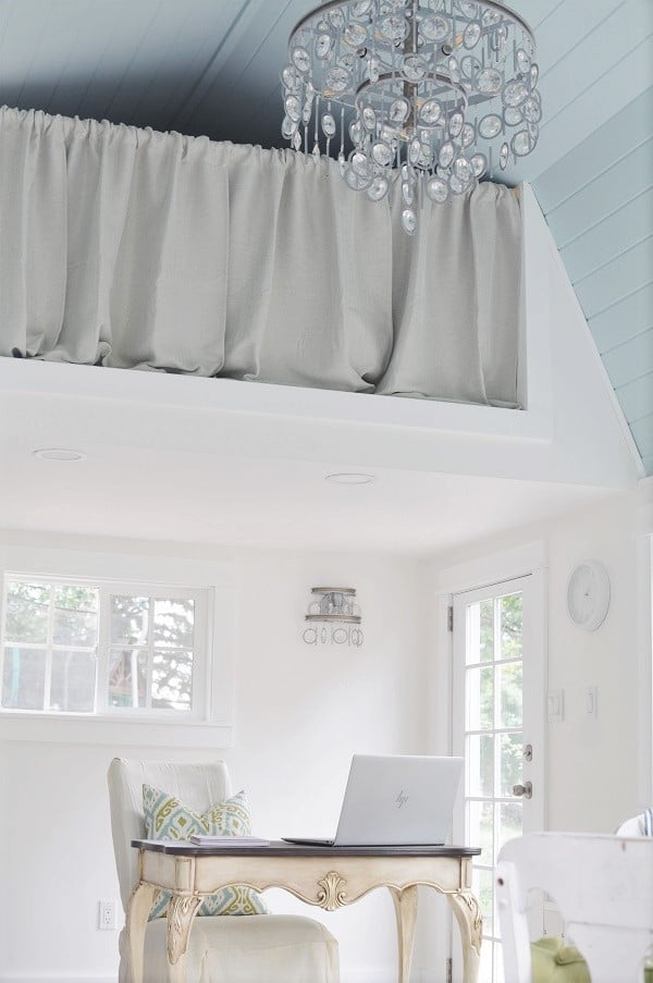 Crystal chandelier hanging from vaulted blue shiplap ceiling with statement light fixtures on the wall.