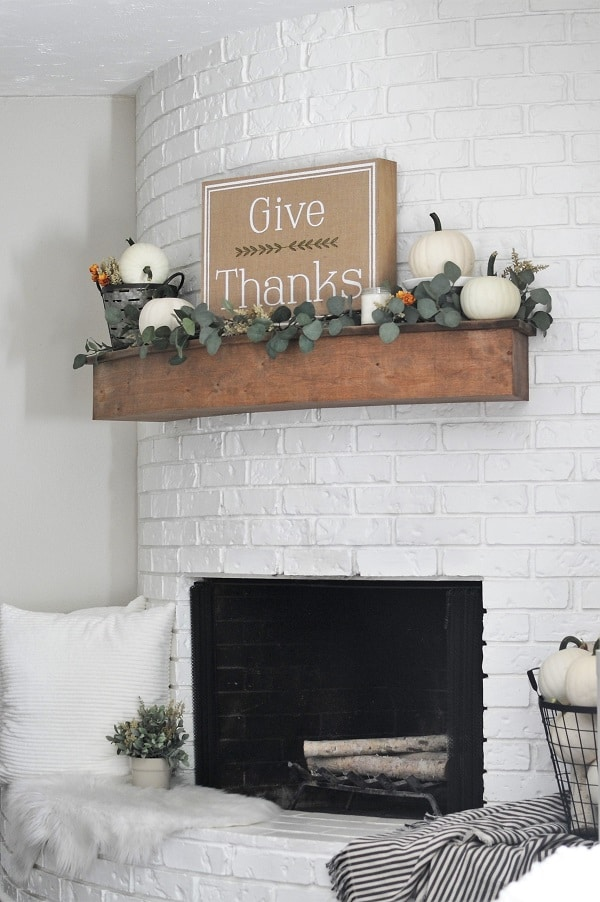 Round fireplace with mantel and hearth decorated in neutral fall decor.