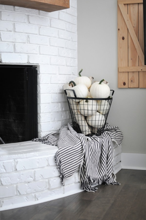 Black metal basket full of white pumpkins in a neutral fall decor home tour.