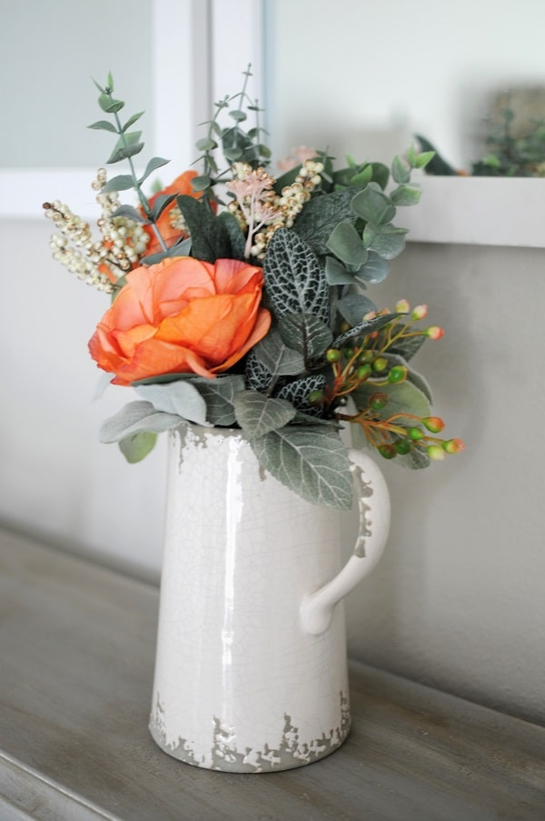 Beautiful bouquet of greenery and orange roses in a white pitcher for neutral home decor option.