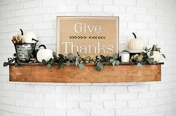 Wood mantel on white brick fireplace decorated with white pumpkins and greenery.